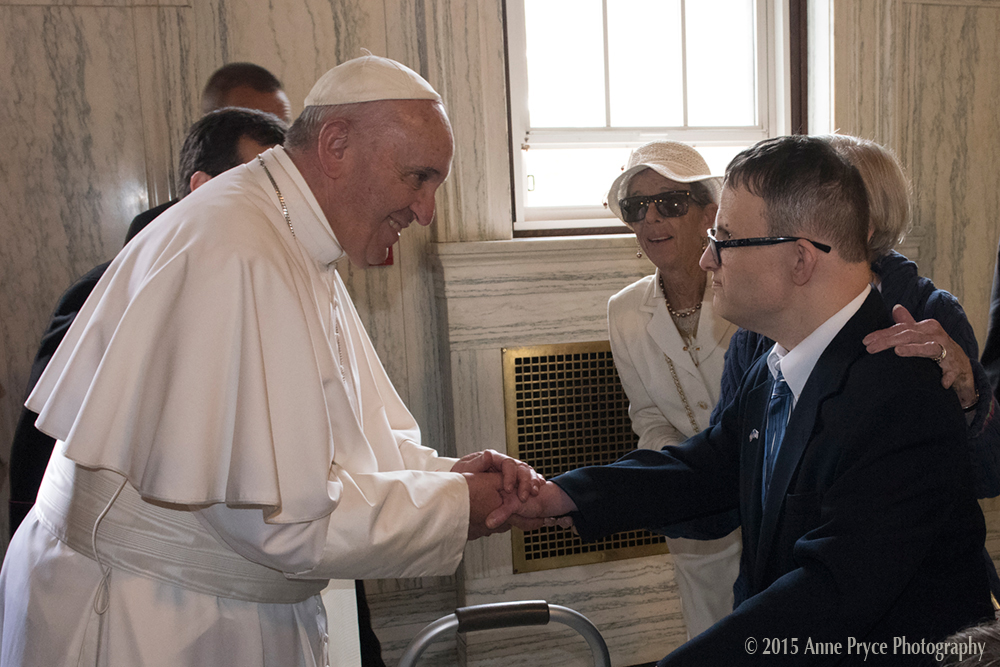 Pope shaking hands with young adult in suit
