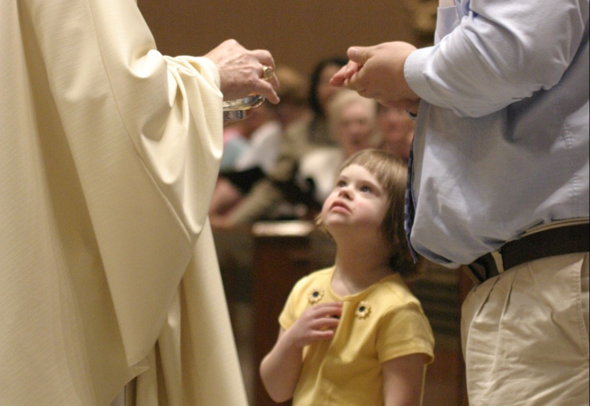 young girls with downsyndrome with father receiving communion